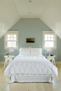 Dormitor amenajat la mansarda cu pat din fier vopsit in alb