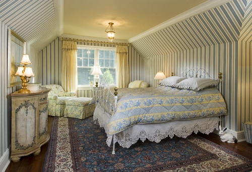 Dormitor clasic cu pat din fier forjat alb si tapet pe pereti in dungi gri bleu cu alb si maro