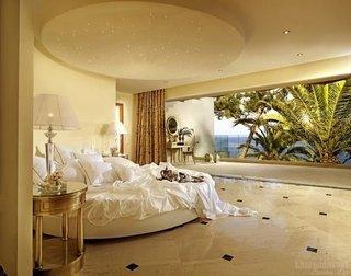 Amenajare de lux dormitor cu pat circular si mobilier auriu