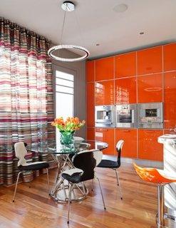 Bucatarie cu mobila portocalie lucioasa si perdea lunga in dungi asortate