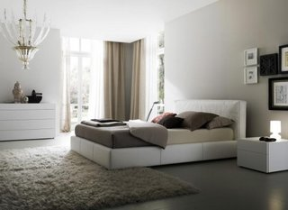 Dormitor cu geam mare pe colt si perdea si draperie in nuante neutre