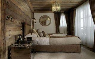 Dormitor rustic cu perete si tavan placate cu lemn si draperii asortate