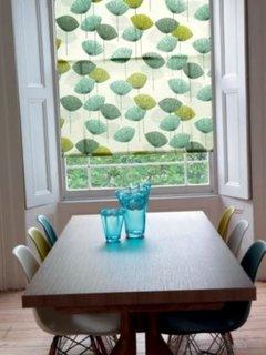 Masa de bucatarie din lemn scaune colorate si roleta textile asortata cu nuantele scaunelor