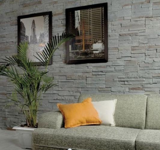 Canapea gri asortat cu perete placat cu piatra decorativa si tablouri
