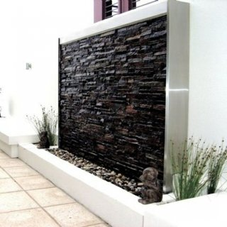 Rond de flori decorat cu perete din piatra cu apa