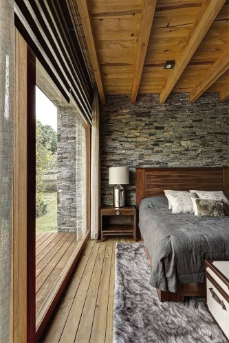 Dormitor cu grinzi din lemn si perete din piatra