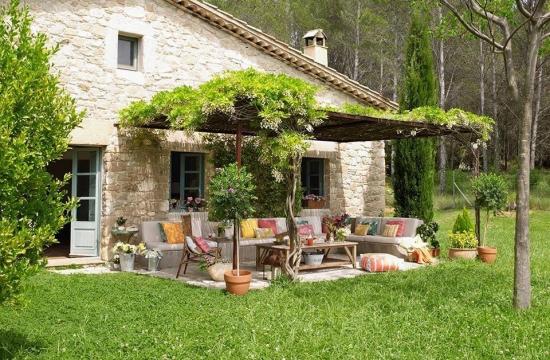 Pergola langa casa acoperita cu plante agatatoare