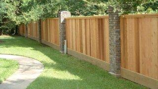Gard cu stalpi din beton placati cu piatra si lemn