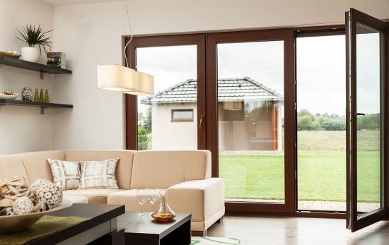 Living cu ferestre mari amenajat cu canapea crem