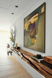 Living cu etajera suspendata pe perete realizata dintr-un trunchi de cops