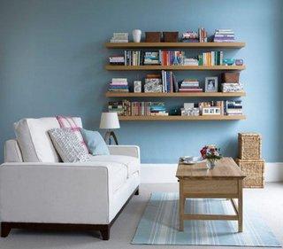 Living zugravit bleu cu masuta de cafea din lemn si etajere de perete suspendate