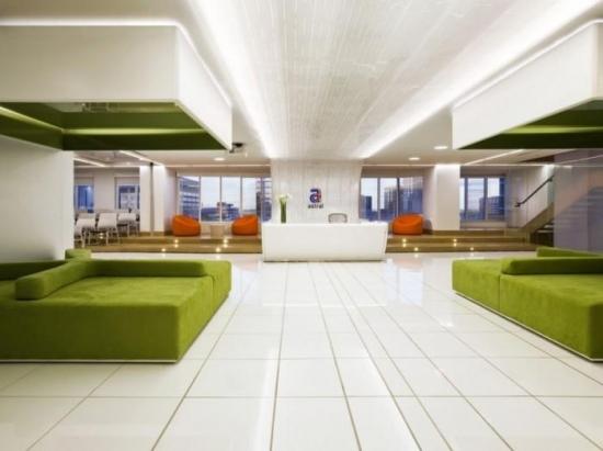 Idee de amenajare a unui hol de asteptare cu canapele verzi si birou alb pentru receptie