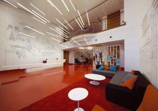Pardoseala rosie din beton slefuit pereti albi si canapele gri varianta de amenajare a unei sali de