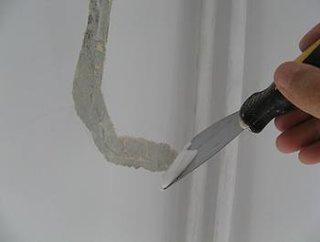 Aplicare cu spaclul a unui strat de glet peste fisura