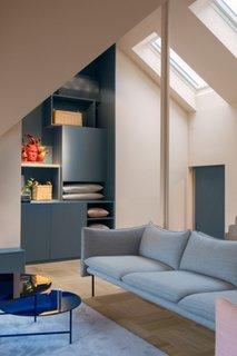 Camera cu tavan inclinat cu canapea si covor bleu