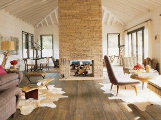 Living decorat in culori neutre cu semineu cu piatra in centrul camerei