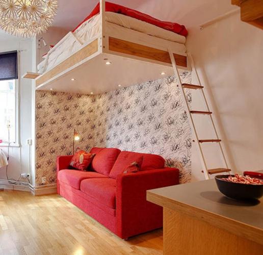 Canapea rosie cu pat suspendat deasupra solutie pentru spatii mici