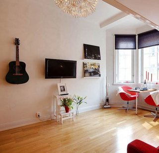 Televizor pe perete incadrat de tablouri si o chitara