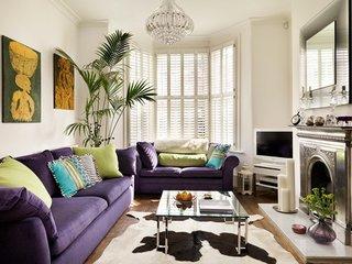 Living amenajat cu doua canapele mov cu perne colorate