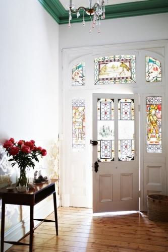 Usa de intrare alba cu ferestre cu vitralii colorate un detaliu mereu la moda