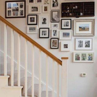 Peretele cu scara interioara amenajat cu o colectie de tablouri