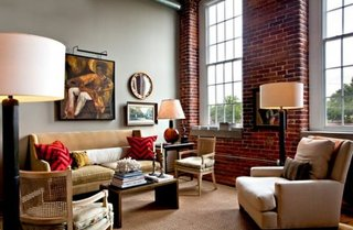 Living cu perete lateral placat cu caramida rosie