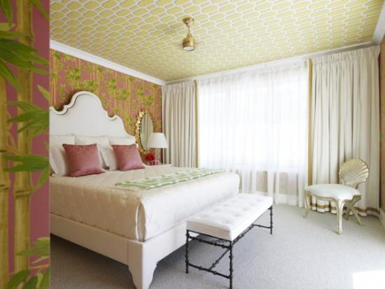 Dormitor cu perete de accent cu tapet roz cu galben si tavan asortat