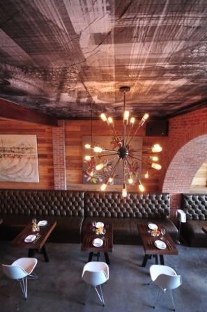 Restaurant amenajat in stil industrial cu tapet pe tavan cu aspect metalic