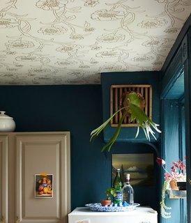 Tapet alb cu model floral auriu combinat cu pereti albastru inchis in bucatarie