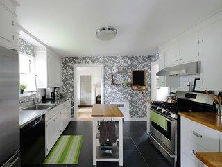 Decor modern de bucatarie cu mobila alba blat de lucru din lemn si tapet gri cu flori albe