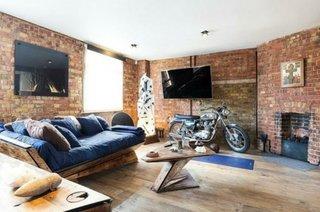 Living amenajat in stil minimalist industrial cu peretii placati cu caramid rosie