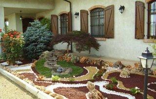 Aranjament cu pietris maro si alb in gradina de langa casa