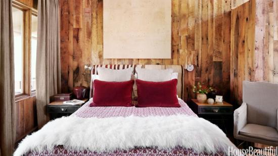 Dormitor cu pereti din lemn si pat mare cu tesaturi pufoase