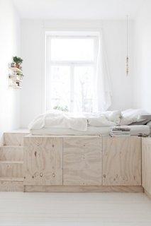 Dormitor amenajat pe platforma de lemn inaltata prevazuta cu spatii de depozitare