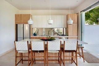 Bucatarie cu mobilier in doua culori si insula de bucatarie cu scaune albe