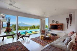 Living cu canapea pe platforma de lemn si vedere catre piscina si munti