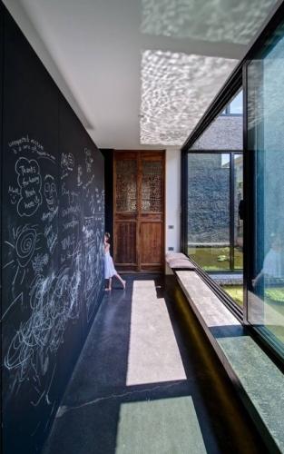 Hol lung cu ferestre mari si perete negru tabla de scris