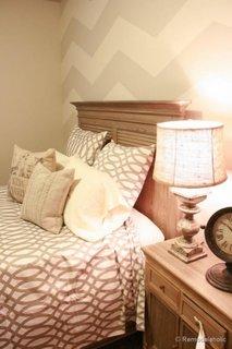 Dormitor cu perete de accent zugravit in doua culori gri si crem