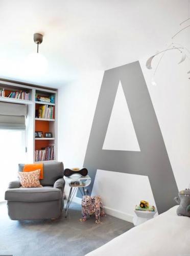 Living cu perete de accent cu litera mare zugravita cu gri pe fundal alb